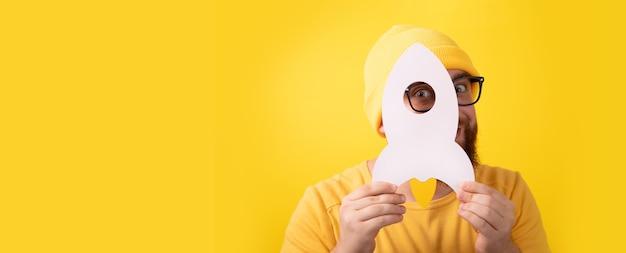 Mężczyzna trzymający rakietę na żółtym tle, koncepcja udanego uruchomienia, układ panoramiczny