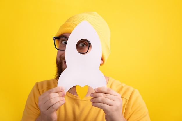 Mężczyzna trzymający rakietę na żółtym tle, koncepcja udanego uruchomienia