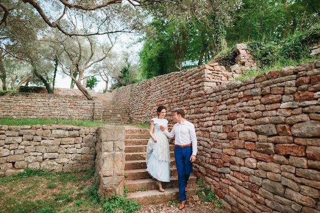 Mężczyzna trzymający rękę kobiety pomagający schodzić po kamiennych schodach w zielonym gaju oliwnym