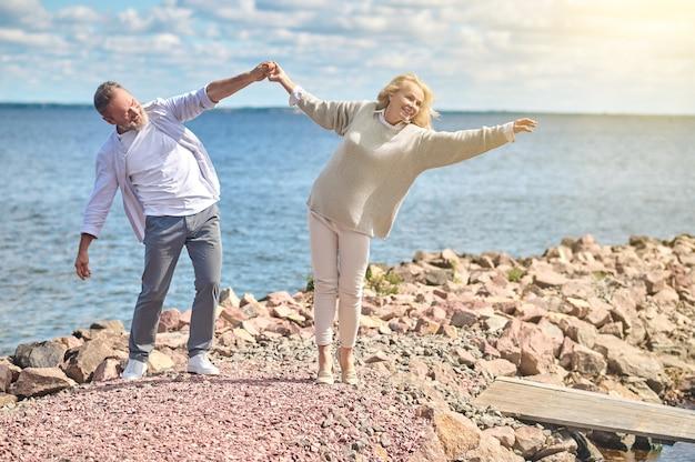 Mężczyzna trzymający rękę kobiety sięgający po słońce