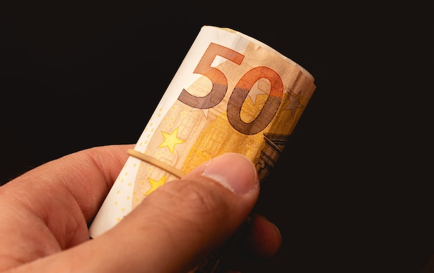 Mężczyzna trzymający rolkę banknotów euro na zdjęciu z czarnym tłem