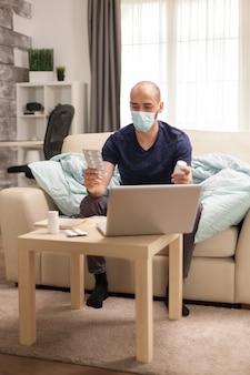 Mężczyzna trzymający różne tabletki podczas konsultacji online z lekarzem w kwarantannie.