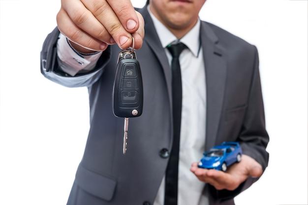 Mężczyzna trzymający samochodzik i klucze na białym tle