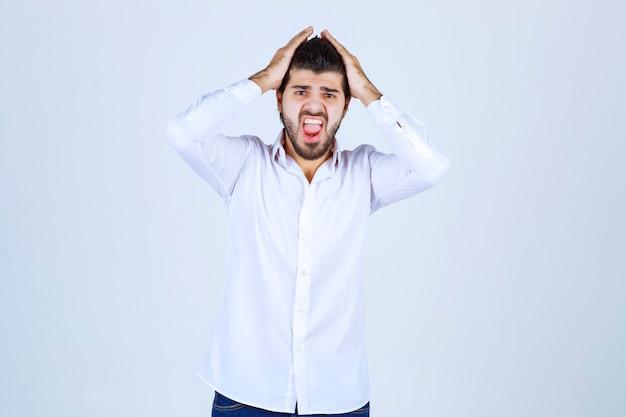 Mężczyzna trzymający się za głowę dwiema rękami, gdy jest wyczerpany