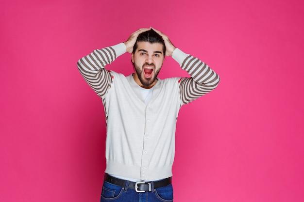 Mężczyzna trzymający się za głowę, gdy jest wyczerpany lub ma ból głowy.