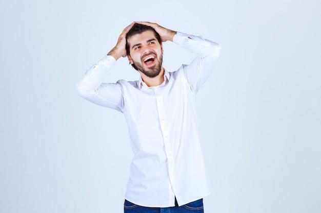 Mężczyzna trzymający się za głowę i śmiejący się głośno