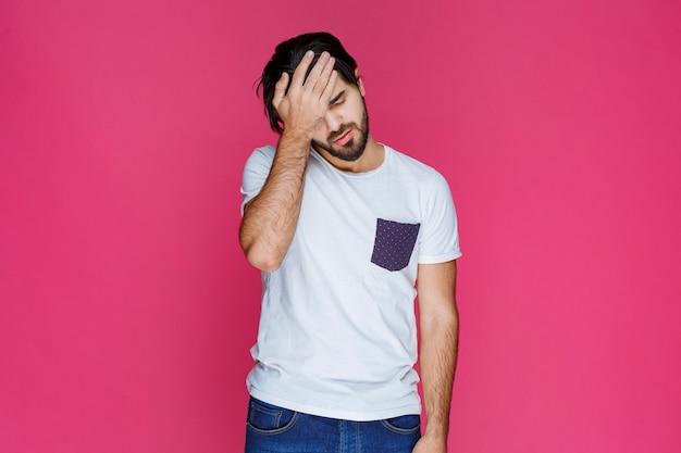 Mężczyzna trzymający się za głowę, jakby miał ból głowy lub duży problem.