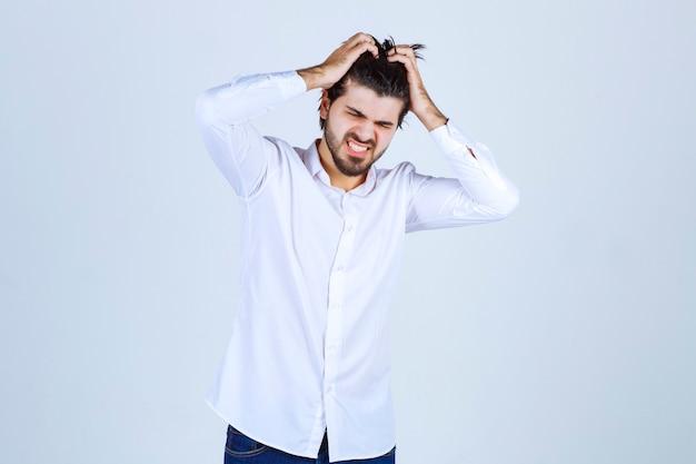 Mężczyzna trzymający się za głowę z powodu bólu głowy lub uczucia wyczerpania