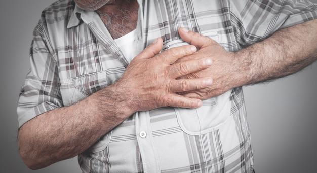 Mężczyzna trzymający się za klatkę piersiową cierpiący na zawał serca.