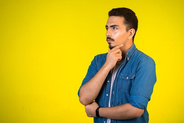 Mężczyzna trzymający się za klatkę piersiową i głęboko myślący o nowym projekcie