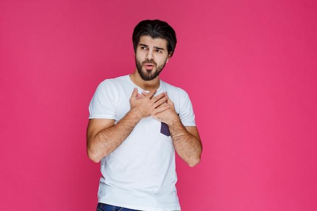 Mężczyzna trzymający się za ręce do klatki piersiowej i wskazujący na siebie.