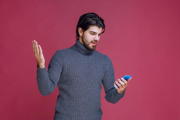 Mężczyzna trzymający smartfon, czytający wiadomości lub wysyłający sms-y.