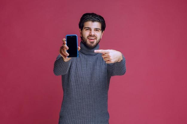 Mężczyzna trzymający smartfon i prezentujący go klientom.