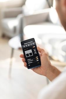 Mężczyzna trzymający smartfon z aplikacją automatyki domowej