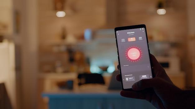Mężczyzna trzymający smartfon z aplikacją do sterowania oświetleniem, włączający światła siedzący w kuchni z systemem automatyki oświetlenia. osoba korzystająca z oprogramowania inteligentnego domu pracująca zdalnie przy laptopie