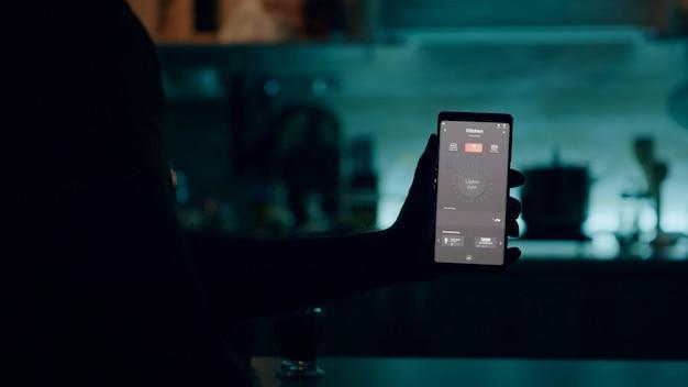 Mężczyzna trzymający smartfon z aplikacją do sterowania oświetleniem, włączający światła siedzący w kuchni z systemem automatyki oświetleniowej