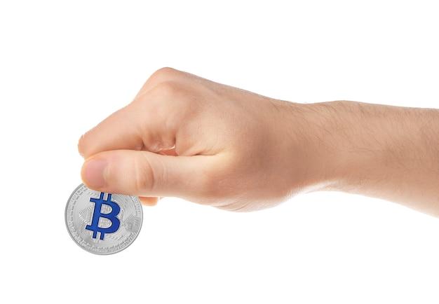 Mężczyzna trzymający srebrnego bitcoina na białej powierzchni