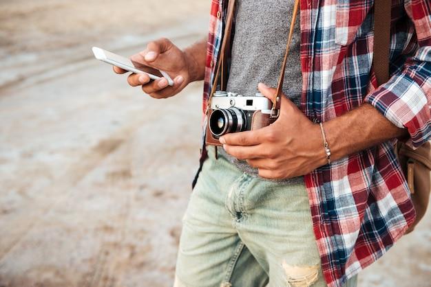 Mężczyzna trzymający stare zdjęcie z przodu i używający telefonu komórkowego na zewnątrz