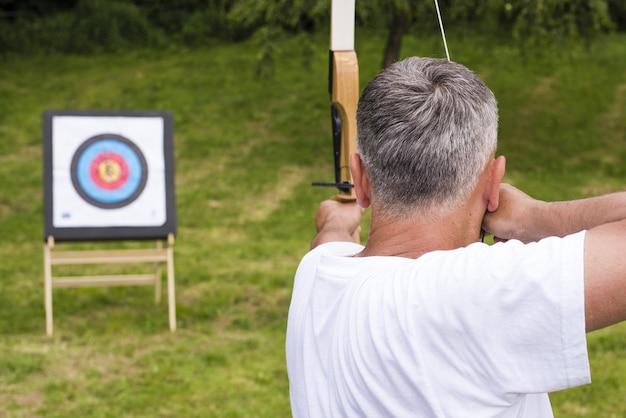 Mężczyzna trzymający strzałę i grający w docelową grę łuczniczą