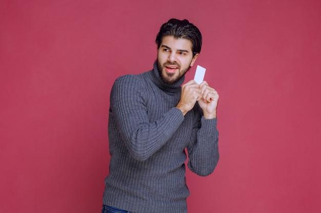Mężczyzna trzymający swoją wizytówkę, czujący się bardzo pozytywnie i pewnie siebie.