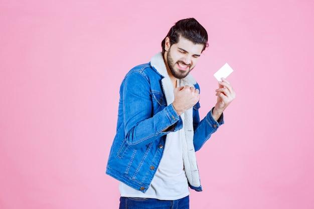 Mężczyzna trzymający swoją wizytówkę i czujący się jak zwycięzca