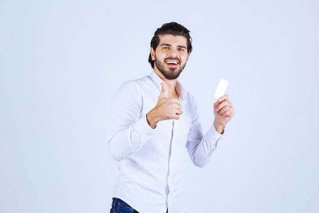 Mężczyzna trzymający swoją wizytówkę i pokazujący kciuk w górę