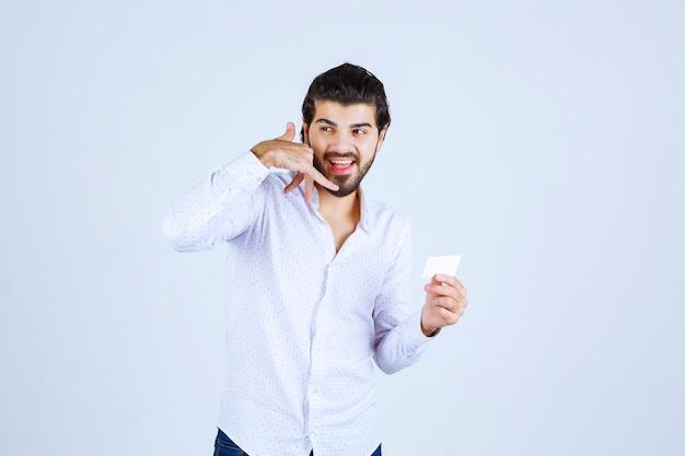 Mężczyzna trzymający swoją wizytówkę i proszący o telefon