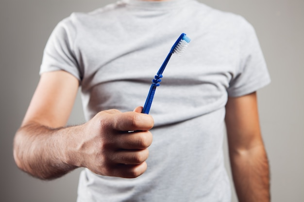 Mężczyzna trzymający szczoteczkę do zębów na szarym tle
