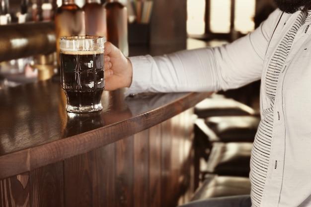 Mężczyzna trzymający szklankę piwa w pubie, zbliżenie