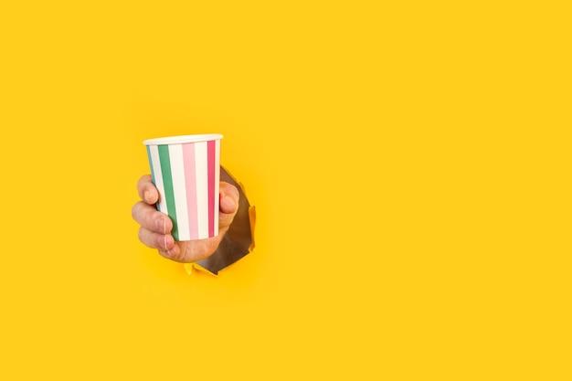 Mężczyzna trzymający szklankę w paski przez żółtą dziurę