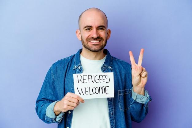 Mężczyzna trzymający tabliczkę powitalną dla uchodźców