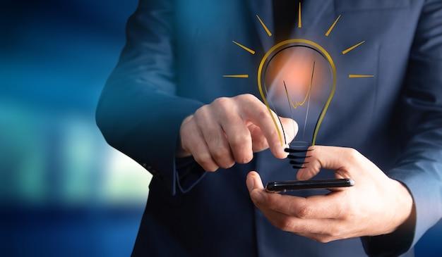 Mężczyzna trzymający telefon z pomysłem lub żarówką