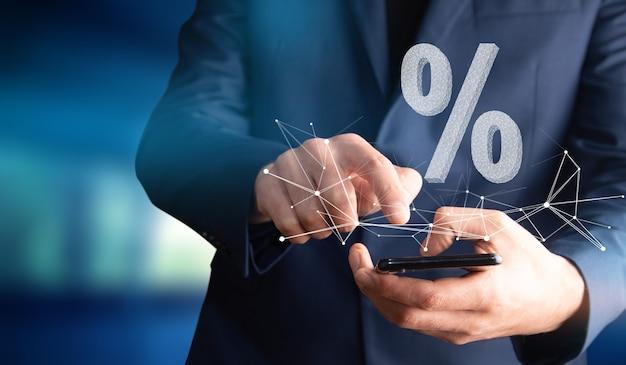 Mężczyzna trzymający telefon ze znakiem procentu lub sprzedaży