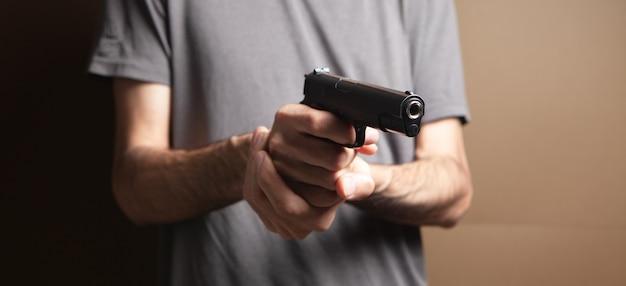 Mężczyzna trzymający w dłoni czarny pistolet grożący