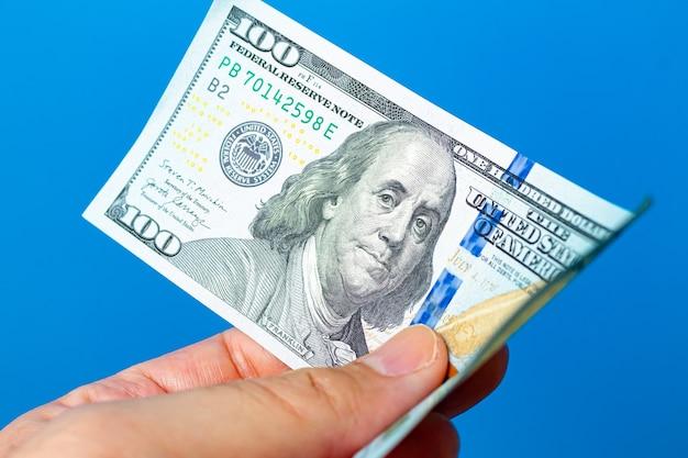 Mężczyzna trzymający wbite banknoty dolarowe z białym tłem