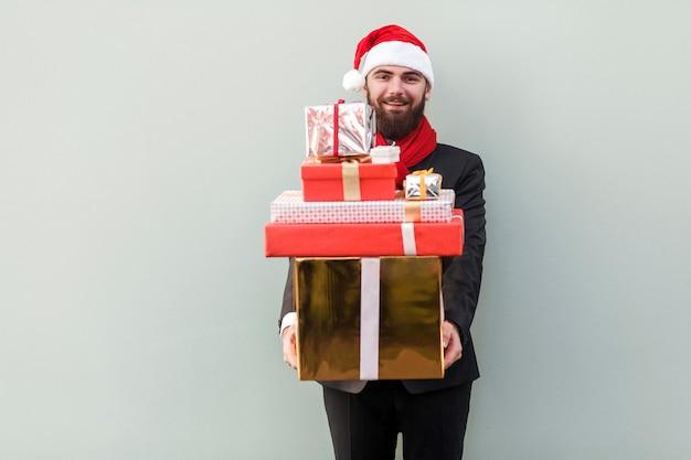 Mężczyzna trzymający wiele pudełek upominkowych i patrzący na aparat i ząbkowany uśmiech na jasnozielonym tle