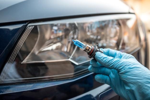 Mężczyzna trzymający żarówkę do naprawy światła samochodowego, reflektora