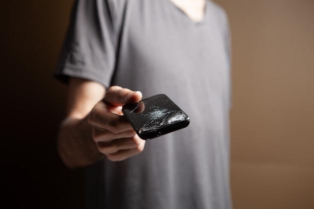 Mężczyzna trzymający zepsuty telefon na brązowym tle