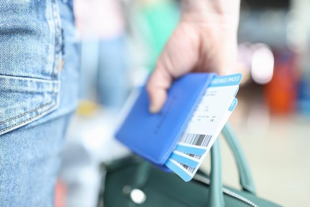 Mężczyzna trzymający zieloną teczkę i paszport z zbliżeniem na bilety lotnicze