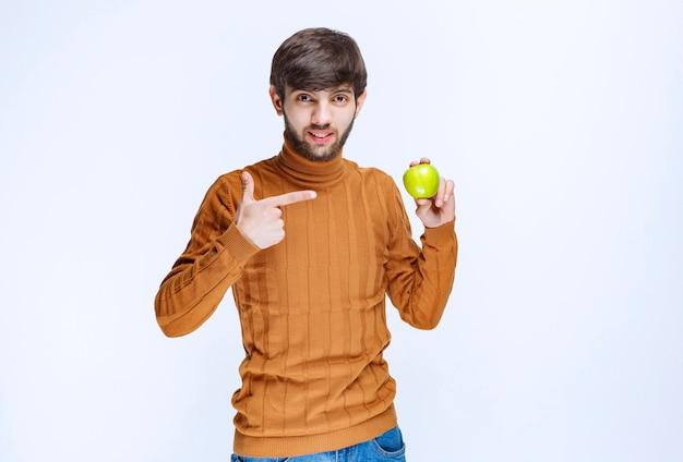 Mężczyzna trzymający zielone jabłko i promujący go wśród klientów.