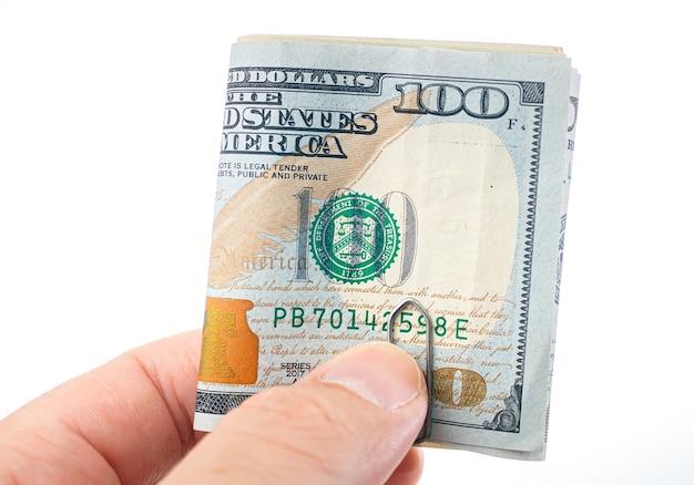 Mężczyzna trzymający złożone banknoty dolarowe na białym tle