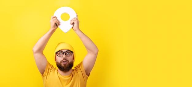 Mężczyzna trzymający znacznik lokalizacji na żółtym tle, koncepcja nawigacji i eksploracji, obraz panoramiczny