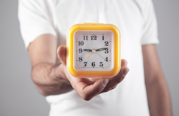 Mężczyzna trzymający żółty zegar