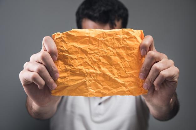 Mężczyzna trzymający żółty zmięty papier jako ściana na szarej ścianie