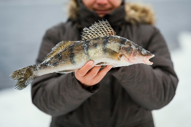 Mężczyzna trzymający zwycięsko złowioną rybę
