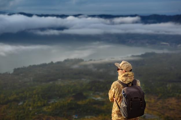 Mężczyzna turysta patrzy na wschód słońca na wulkan batur na wyspie blai w indonezji. wycieczkowicza mężczyzna z plecakiem podróżuje na odgórnym wulkanie, podróży pojęcie