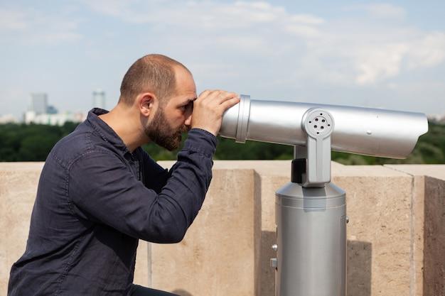 Mężczyzna turysta stojący na dachu budynku patrząc przez teleskop lornetkowy