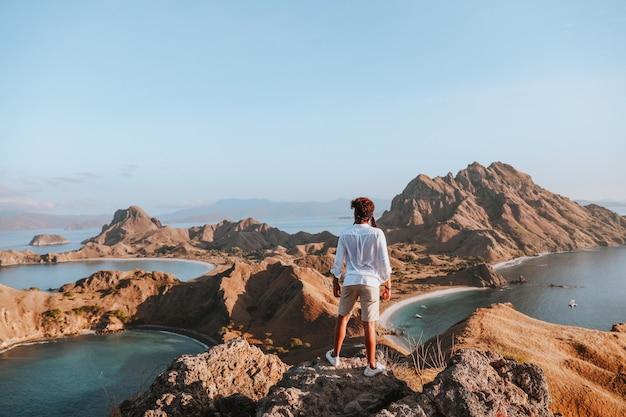 Mężczyzna turysta w białej koszuli stojący na szczycie góry skalnej, podziwiając widok na morze i wzgórze