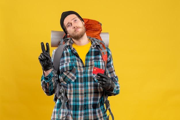 Mężczyzna turysta z backpackerem trzymającym kartę kredytową, czyniąc znak zwycięstwa