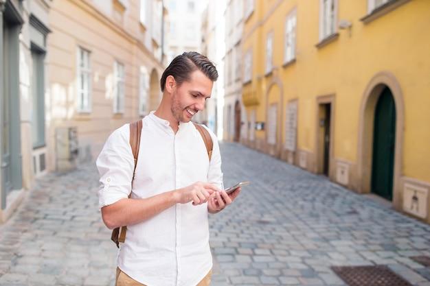 Mężczyzna turysta z plecakiem w europie ulicy. kaukaski chłopiec patrząc z mapą europejskiego miasta.